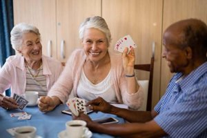 Conservatory At Champion Forest Residents Enjoying Card Game